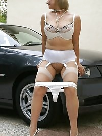 Lusty darling poses next to her car